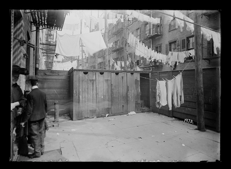 Rear yard in 1902 with four outhouses adjacent to each other in an open area and multiple rows of laundry hanging on clothing lines