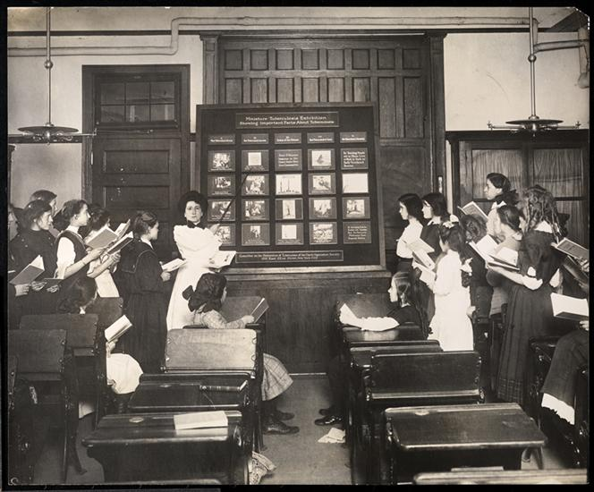 A classroom of young women stand as they take notes on the example being pointed to by their teacher on a chalkboard