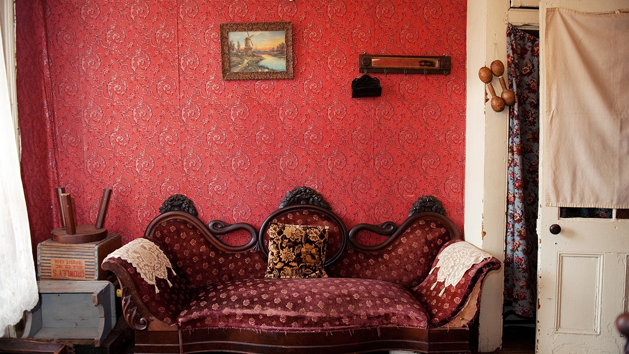 Partial view of Rogarshevsky family parlor with bright red walls, an elegant burgundy couch, and a white wooden sidedoor