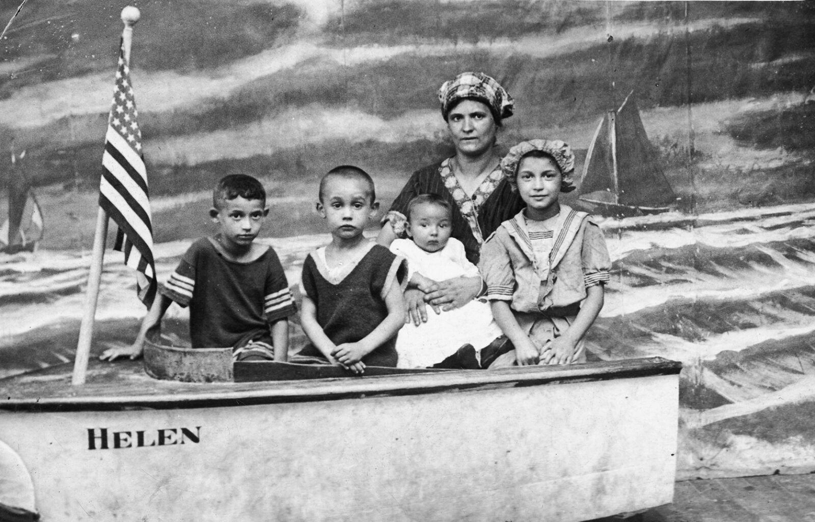 Black and white photo of an adult woman, 3 young children, and a baby posing behind a prop boat and painted ocean background