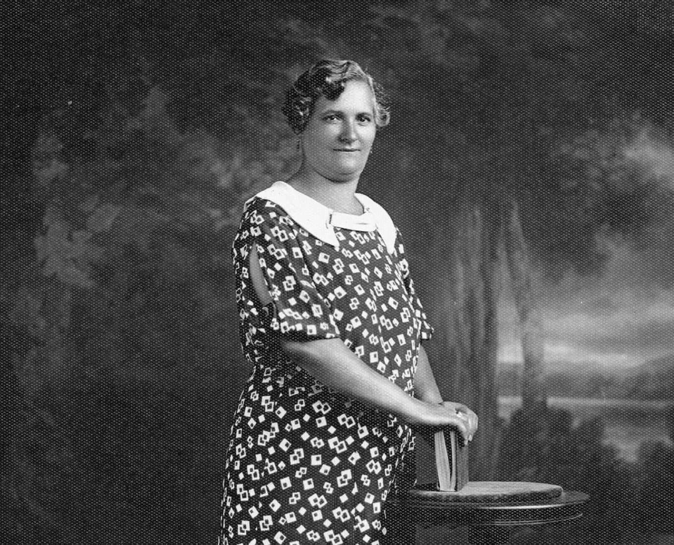 A full-figured adult woman with a light skin tone and short, styled hair poses holding a book in a patterned short-sleeve dress