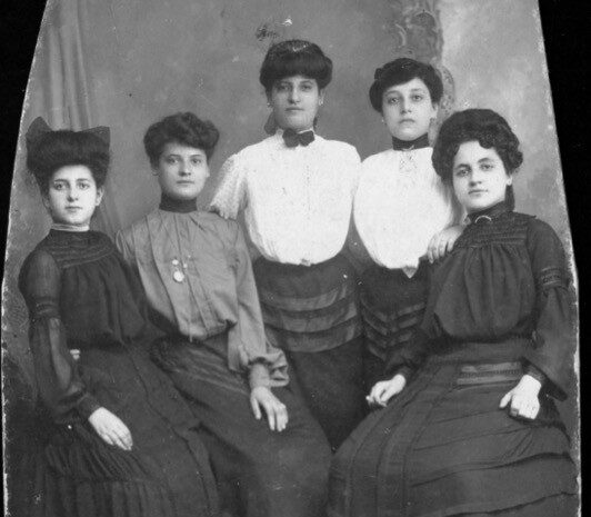 A row of four women with light skin tones and neutral expressions pose together in long-sleeved formal dresses, professional up-dos, and various accessories