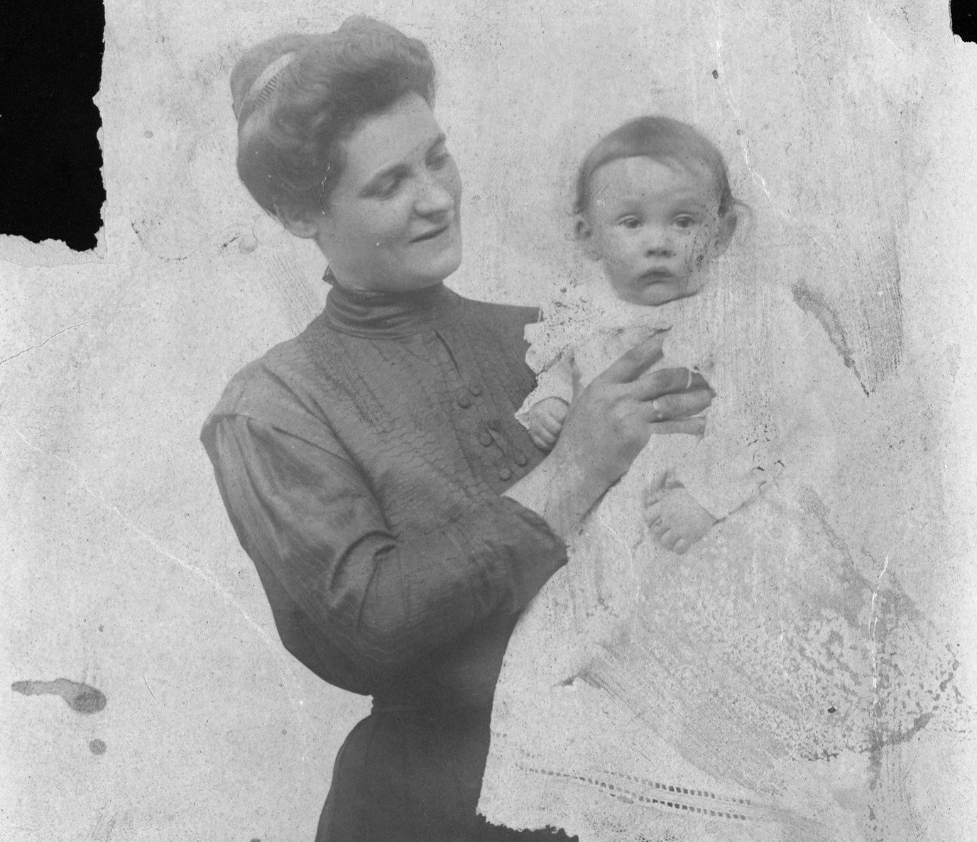 An adult woman in a dark long-sleeved dress and hair in an up-do looks to the baby dressed in white she's carrying on her side