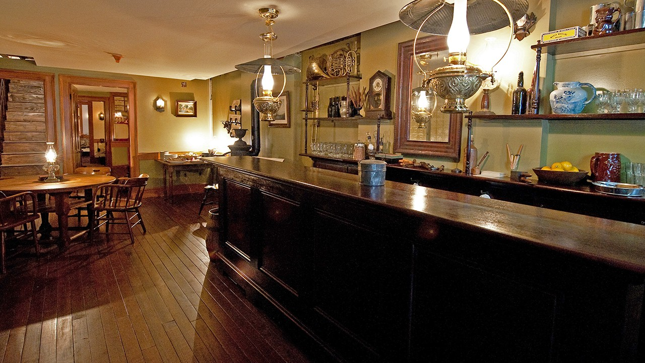Well-lit interior of a bar with a long wooden countertop, circular tables for patrons, and a variety of glass cups and wall decorations
