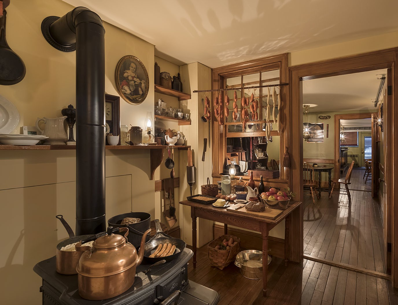 Jars and utensils hang on the wall of a busy kitchen with a large amount of food cooking on an old cast-iron stove and set on a small countertop