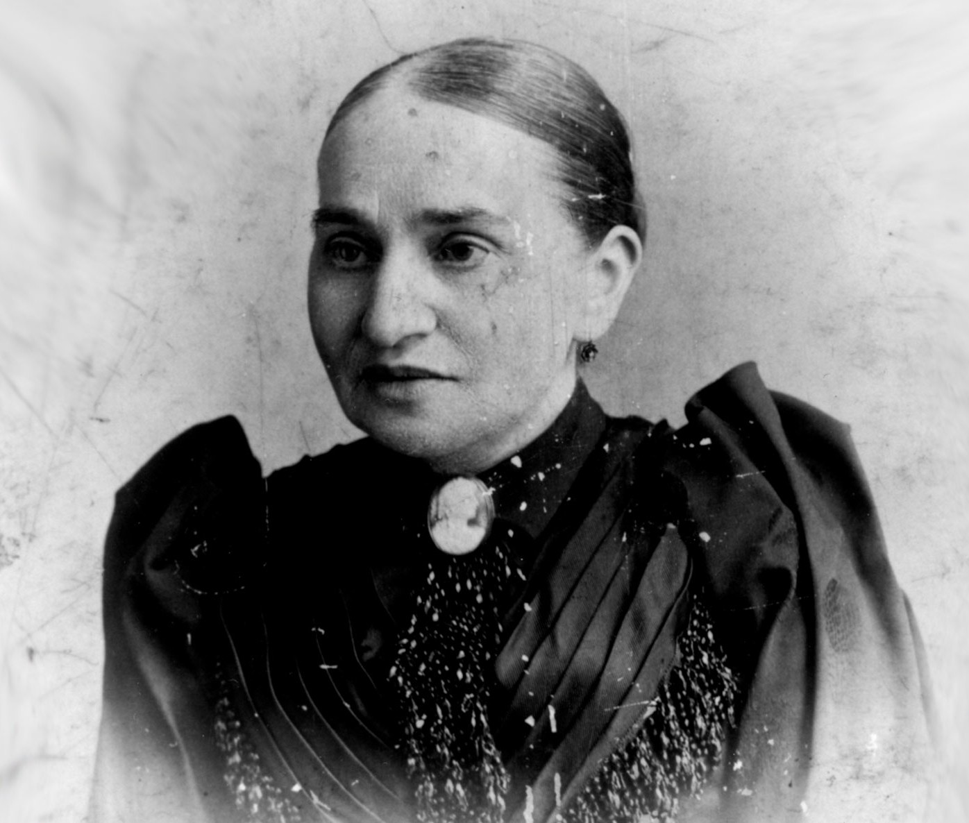 Black and white photo portrait of Natalie Gumpertz wearing her hair pulled back, a brooch, and a black ruffled dress