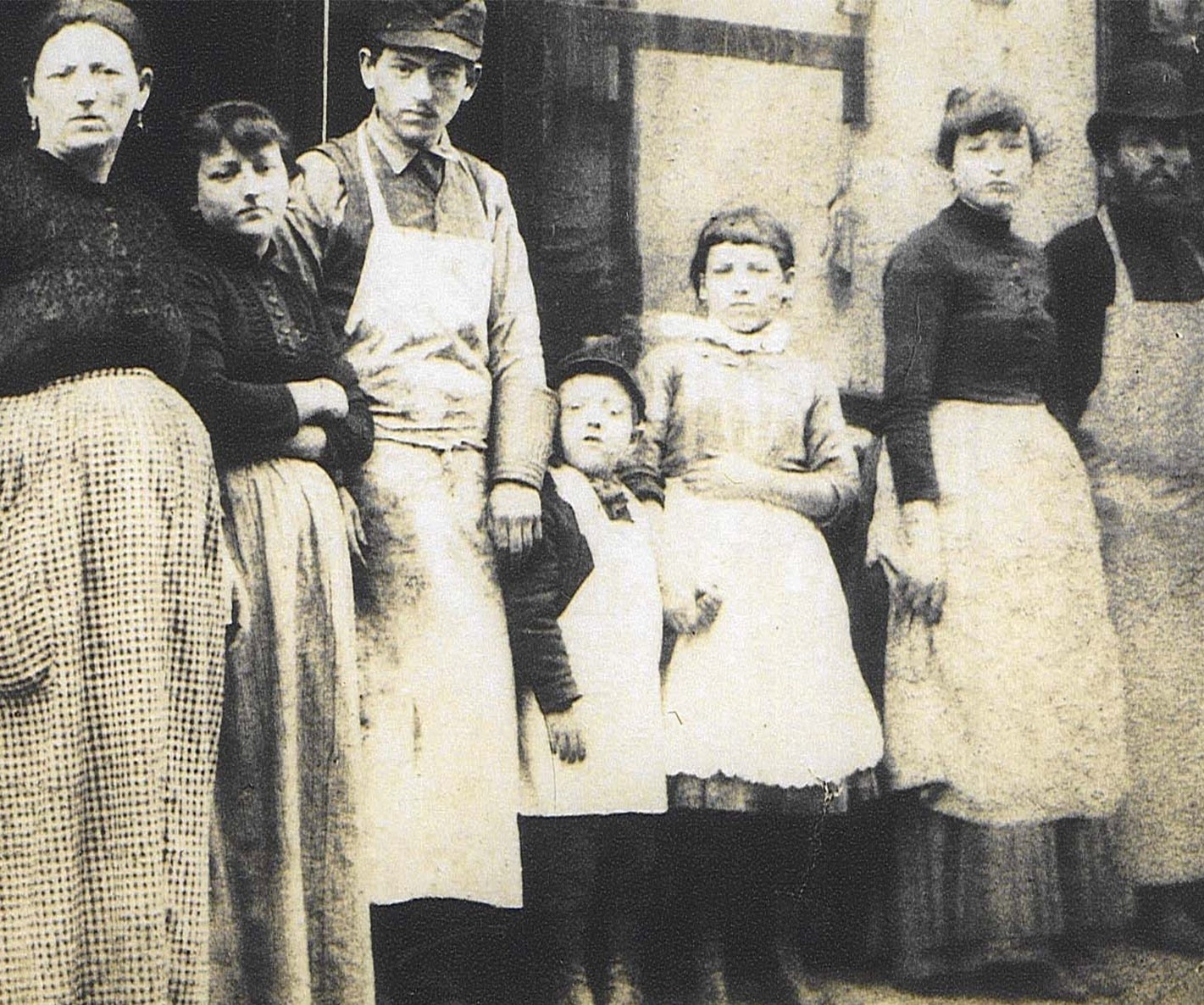 Black and white photo of 7 members of the Lustgarten family with the women and girls in skirts and the men and boys in aprons