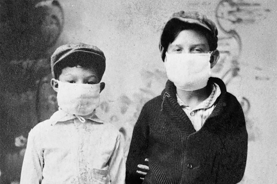 Black and white photo of two children wearing face masks in the early 1900s.