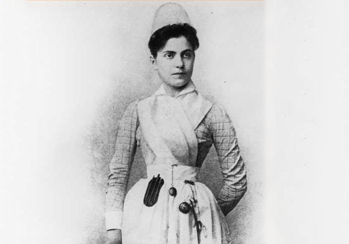 A dark-haired woman stands with a serious expression, a stopwatch and stethoscope hang off the skirt of her white nurse uniform