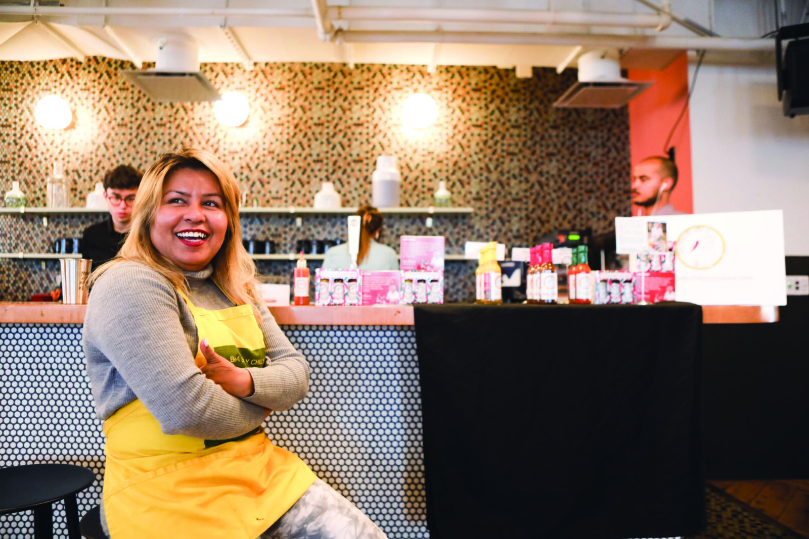 Sufia sits on a stool with her arms folded, smiling, wearing a yellow apron. On the bar behind her are many bottles of hot sauce, with some people busy working behind the bar.