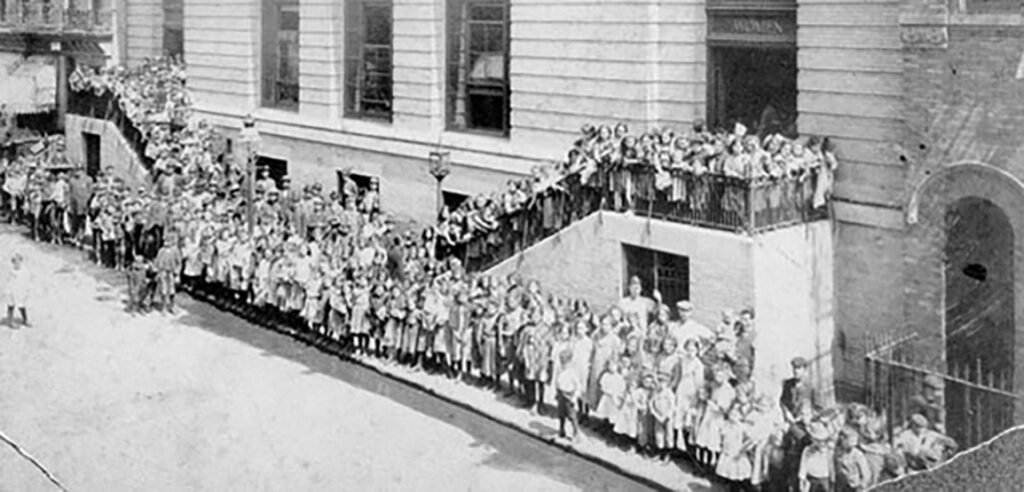 Black and white photo of people in line for a bathhouse on the lower east site in the early 1900s