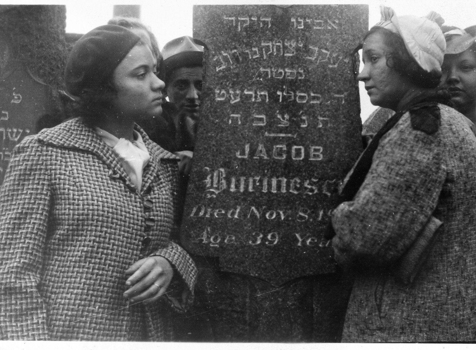 """Black and white photo of two adults with tan skin-tones wearing hats and coats standing on either side of a tombstone inscribed """"Jacob Burinescu"""""""