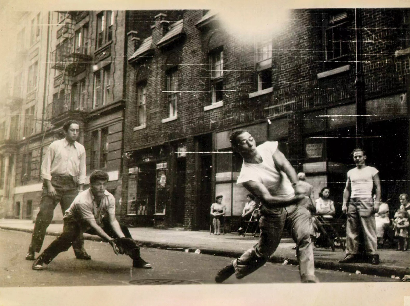 A group of young adults play stickball on the street. The batter takes a swing as the catcher and umpire wait expectantly behind
