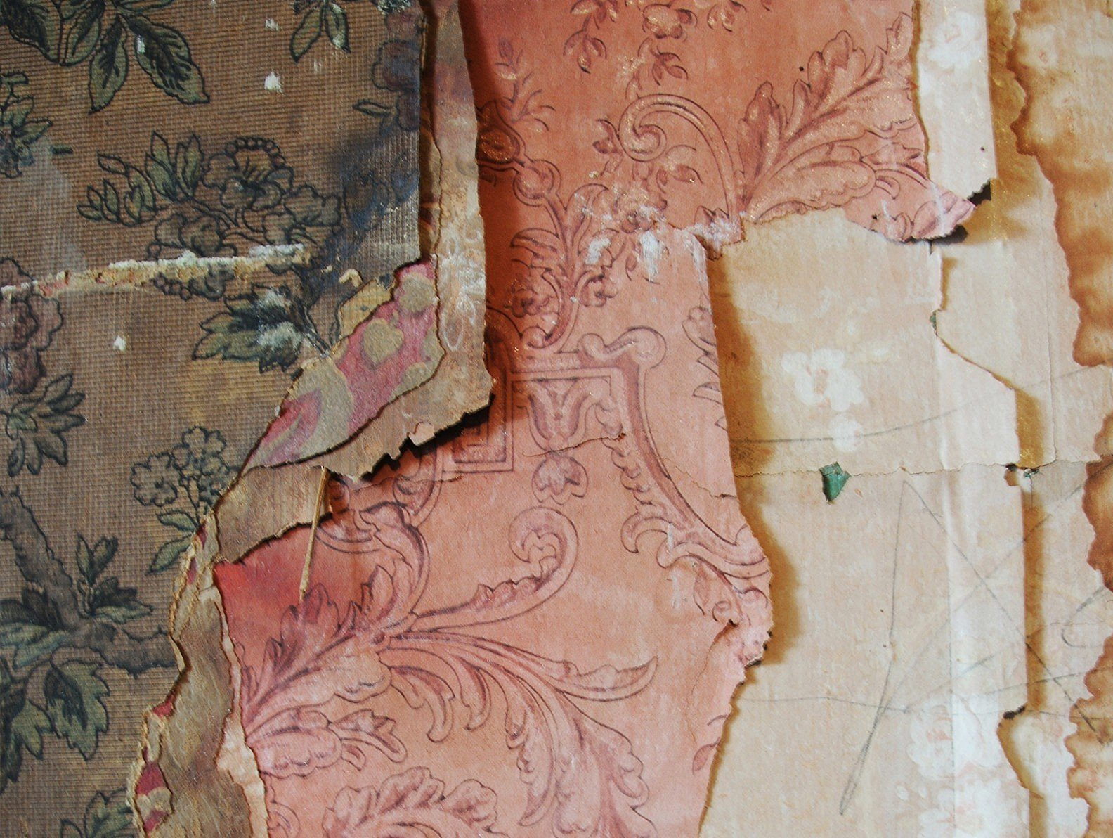 Close up view of various colorfully patterned layers of old wallpaper