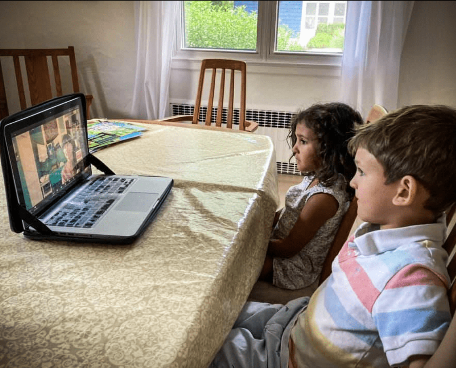 Two young children sit at a dining room table watching a virtual lecture on a laptop.