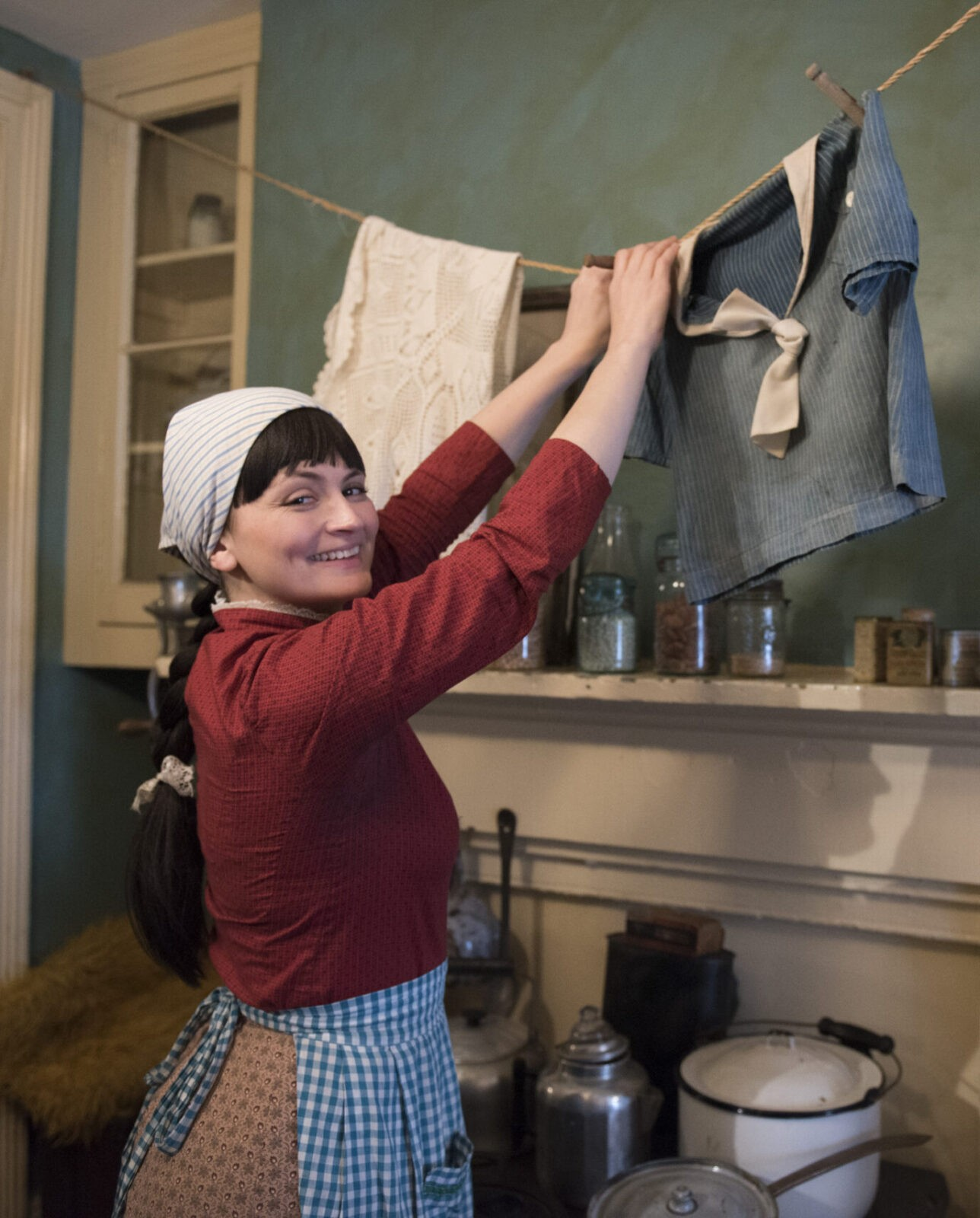 Promotional photo of an actress playing Victoria Confino. Smiling, she wears a headband and blue checkered apron as she hangs clothes on a line hanging in the kitchen of the Confino apartment