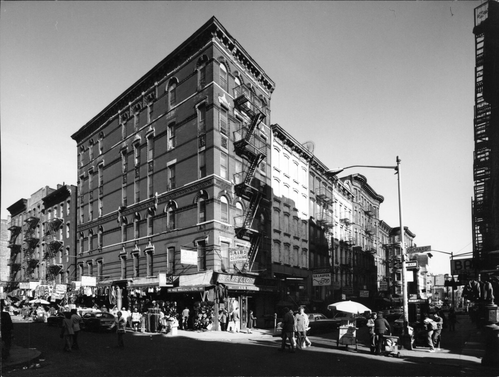 Black and white photo of a street corner in New York City. An apartment building sits at the corner with store fronts on the ground level, people walking by.
