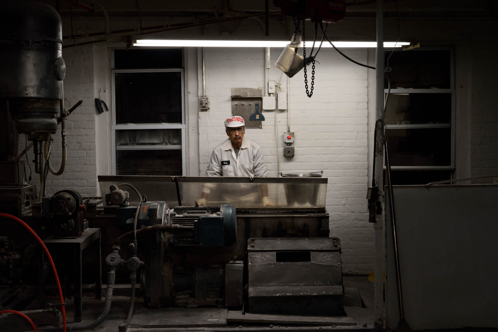Color photo of a Streit's Matzos factory worker looking at the camera, standing behind a large flour mixer under a fluorescent light