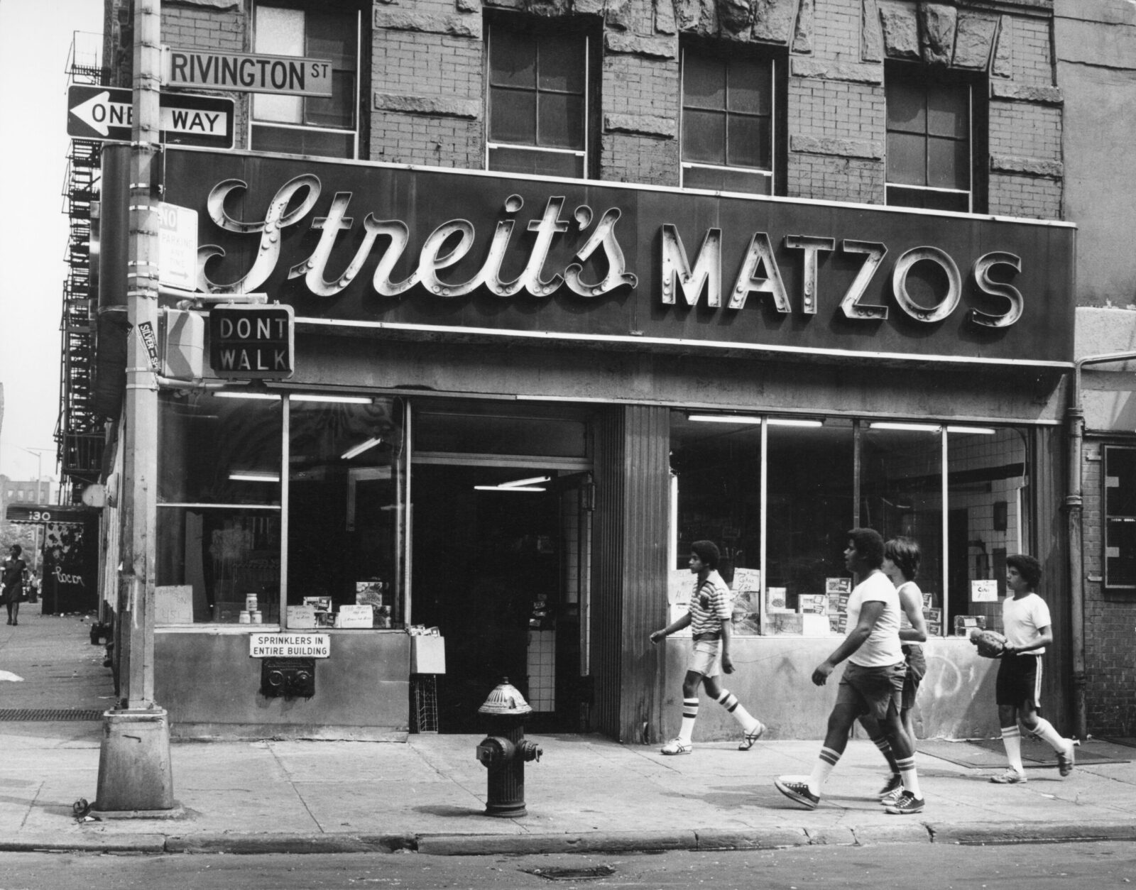 Black and white photo of four young men in shorts and knee socks walking past Streit's Matzos. A street sign labeled Rivington Street is visible.