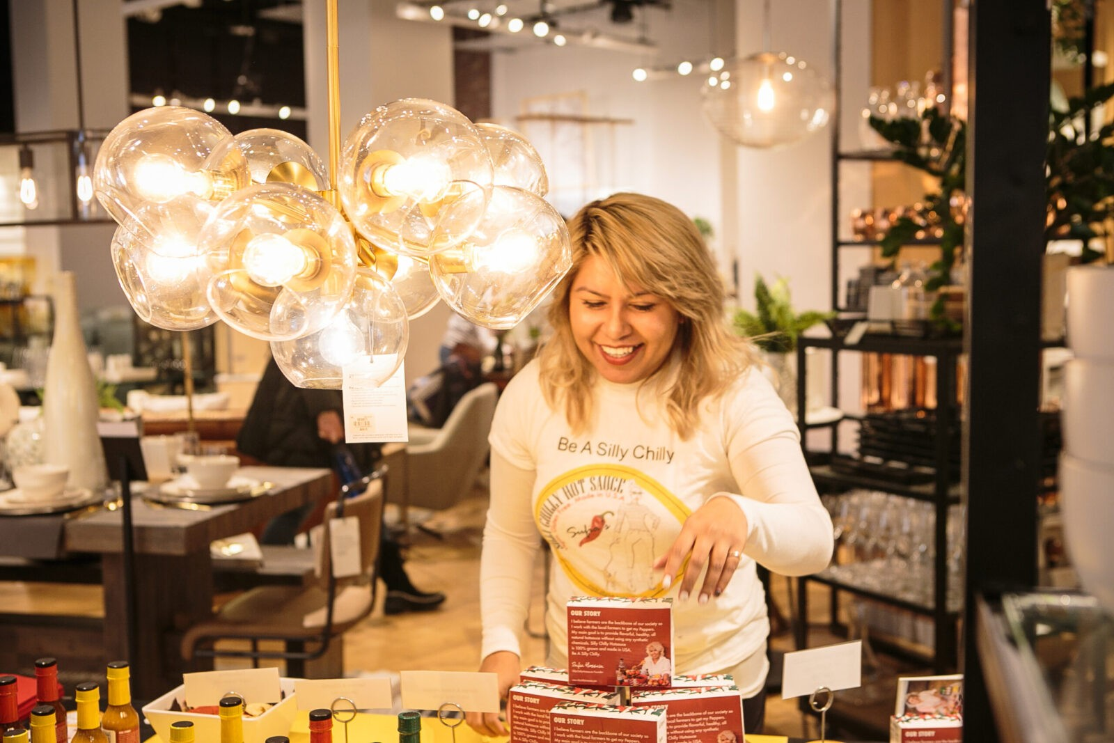 Sufia Hossain, a woman with medium skin and blonde hair, smiles as she arranges a box of hot sauce inside a store, beside a brightly lit lighting fixture