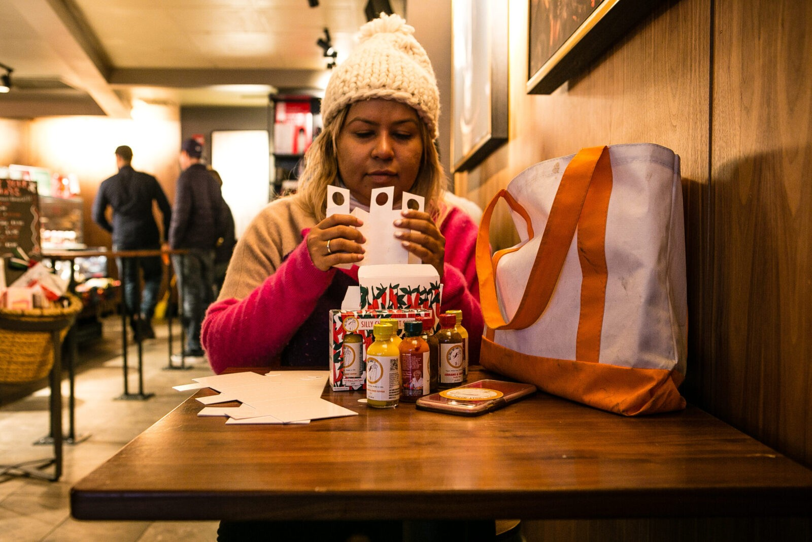 Sufia in a white knit cap sits at a table in a restaurant, folding boxes that hold her hot sauce. A white and orange tote bag sits on the table.