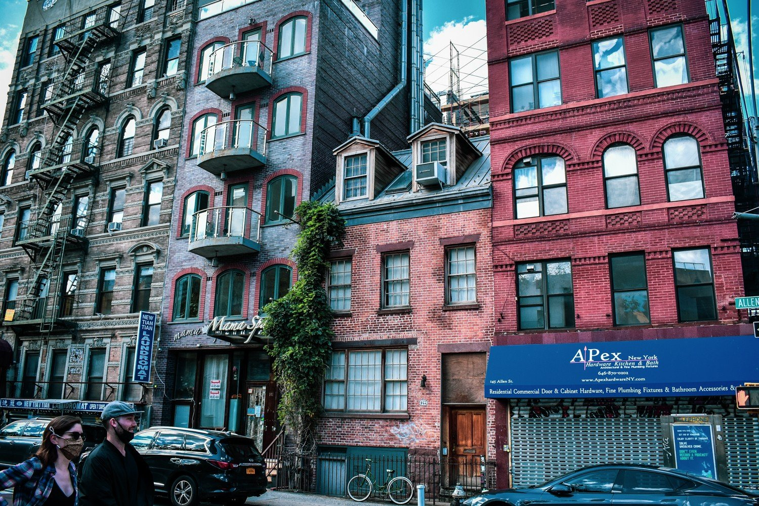 A view of 143 Allen Street; an old 1800s, small 3-story brick building nestled tightly between two other, much taller and newer buildings