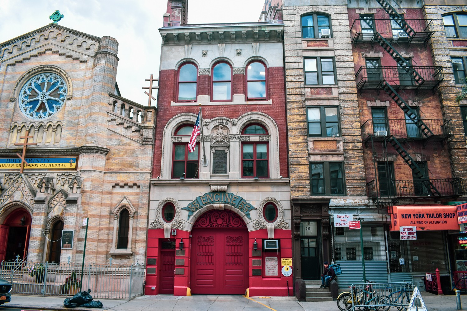 "Exterior of Engine Company 55, a narrow 3-story red brick firehouse. An American flag hangs above a bright red garage door with a placard that reads ""Engine 55"""