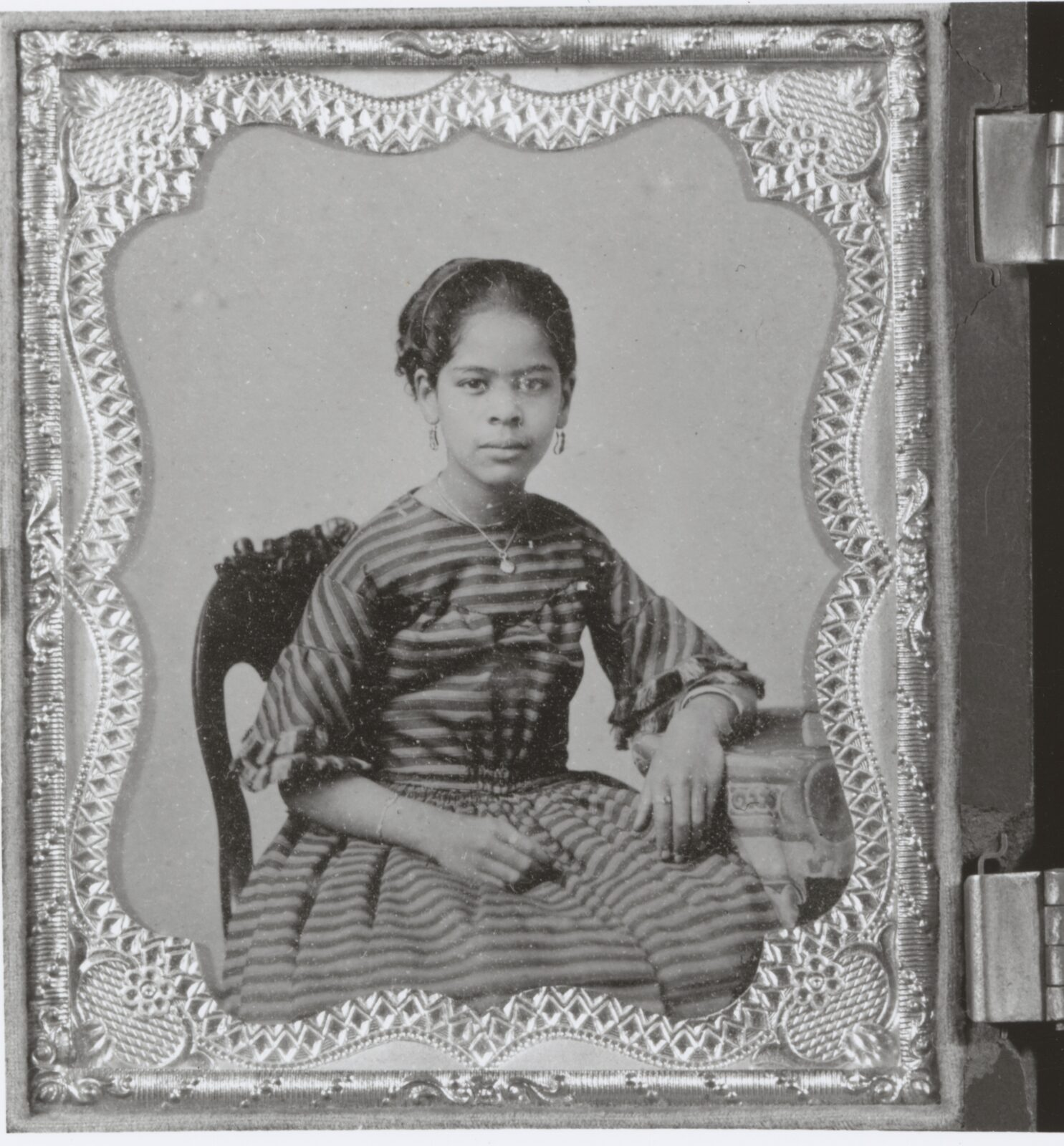 Framed portrait of a young Maritcha Lyons, seated at a table with her hair pulled back in a formal dress with stripes