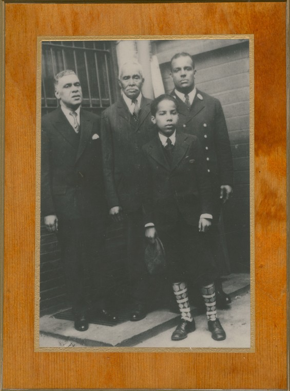 Wesley (back, far right) poses with two other adults and a child, all dressed in formal suits and overcoats