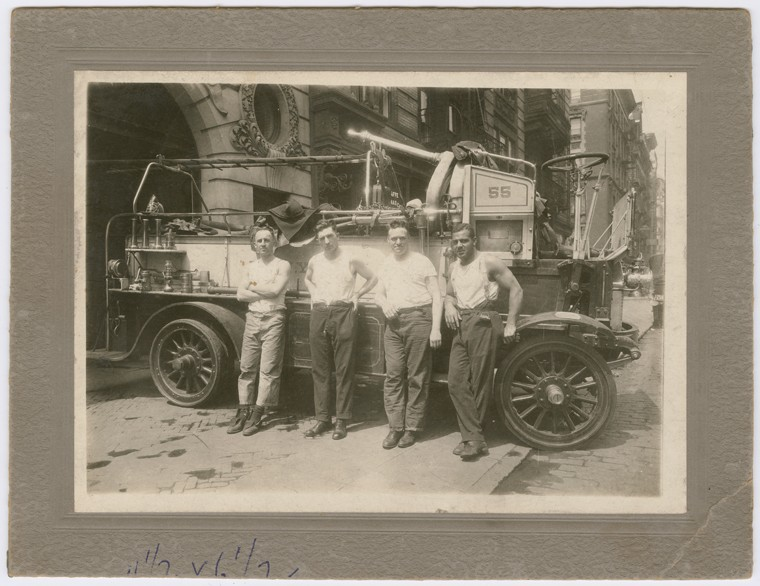 Wesley (far right) stands outside with three other firemen in white t-shirts with their sleeves rolled up, leaning against the side of Fire Engine 55