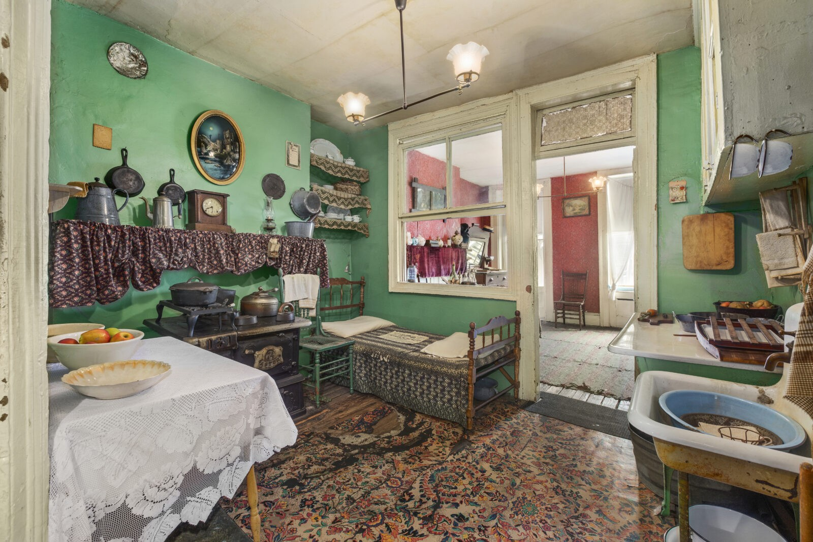 Color photo of the small Rogarshevsky family kitchen at 97 Orchard Street where a table with food is next to a stove, a chair, and a small bed