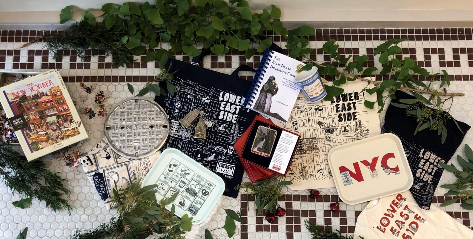 Spread of Tenement Museum merch tote bags, cups, and books