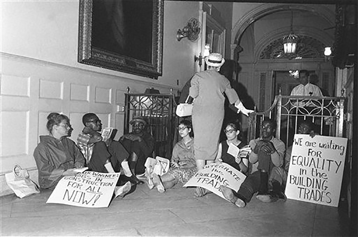 Seven members of CORE, three white, four black, sit inside the entrance of a building a protest signs. A white woman walks through the protesters to enter.