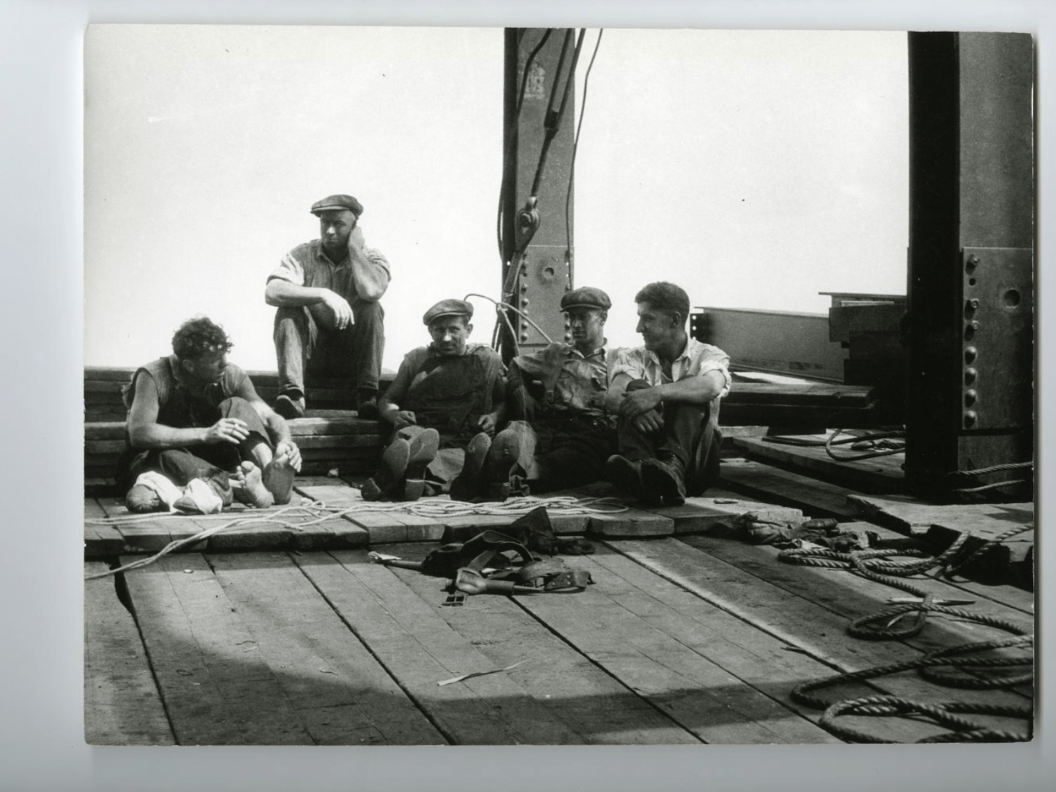 black and white photo of five Mohawk ironworkers in caps and overalls sitting down on a costruction site