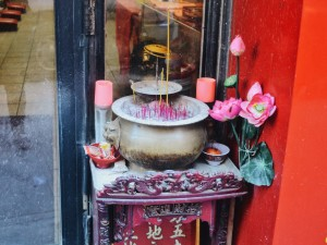 Burning incense outside a Buddhist temple on Broome St.