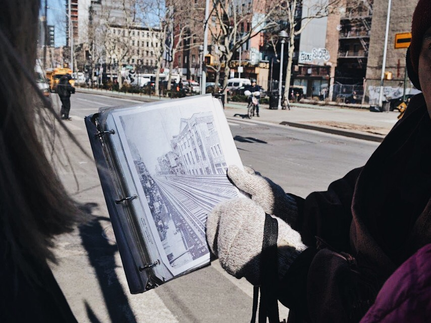Tenement Museum tour guide showing a picture of the old elevated subway track that ran down Allen St.